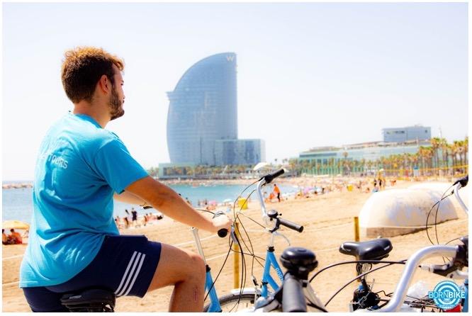 foto de una visita guiada donde vemos personas con sus bicicletas azules, estas son bicicletas de Born Bike Tours Barcelona. Imagen del hotel W.