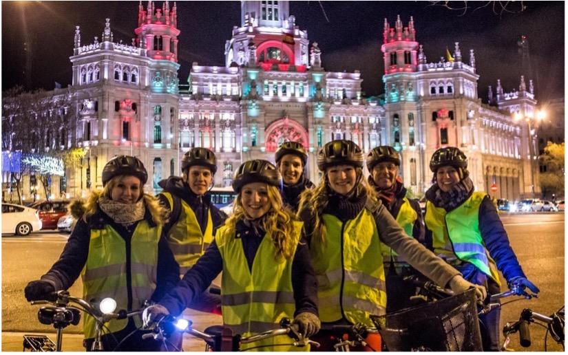 image de sept personnes en gilet jaune avec leur vélo devant un bâtiment illuminé en Espagne
