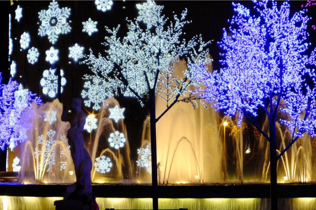 Une image contenant une fontaine d'eau, des arbres, des lumières décoratifs de Noël