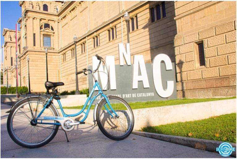 image du musée national d'art de Catalunya avec un vélo bleu de Born Bike Tours Barcelona devant