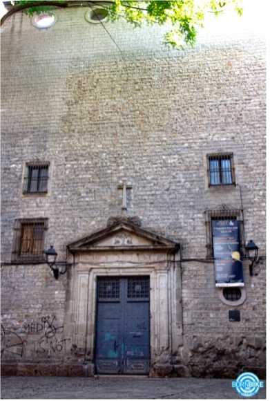 image of a building that contain door, lights, windows, born bike tours Barcelona, text