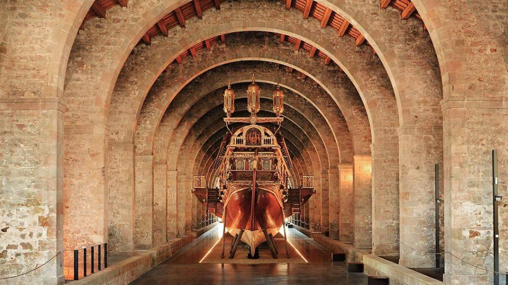 fotografia del interior del museo marítimo en las Drassanes de Barcelona, se ve un majestuoso barco en el centro