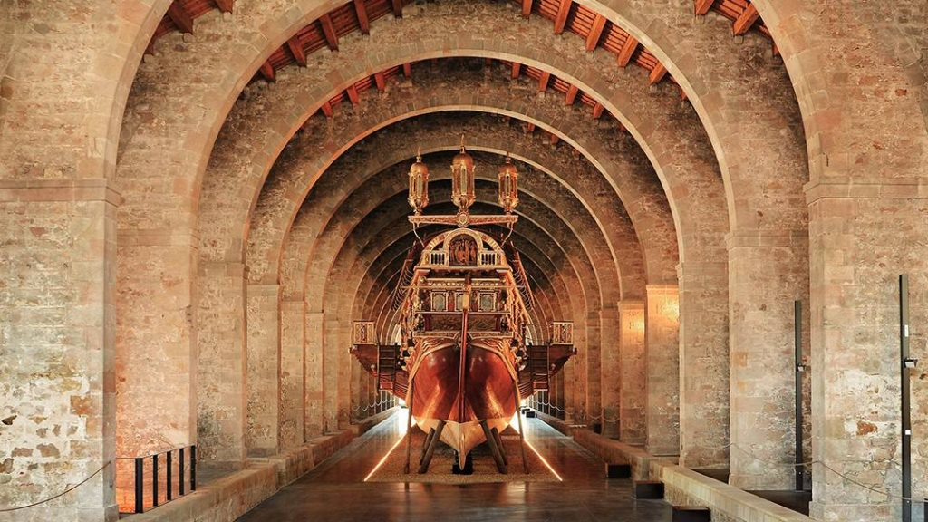 photo de l'intérieur du Musée Maritime dans les Drassanes de Barcelone. On peut voir un majestueux bateau au centre