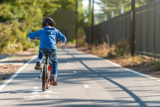 picture of a child riding a bike on a bike lane