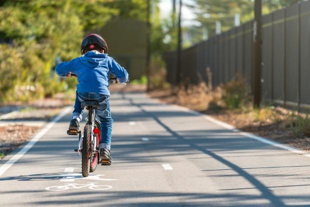 photo d'un enfant sur un vélo sur une piste cyclable